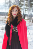 Portrait of red-haired girl in a red raincoat. 