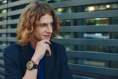 Portrait of red haired man over urban futuristic background. Portrait of young red haired, reddish man with curly hair, gray jacket, blue t-shirt and vintage Stock Images