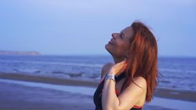 Portrait of a red-haired middle-aged woman in sportswear. A woman walks along the sandy bank of a large river after playing sports stock video footage