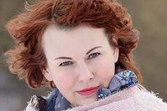 Portrait of a red-haired woman of forty years. On the winter background stock photography