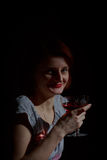 Portrait of red-haired woman with a glass of red wine in the sty Royalty Free Stock Photography
