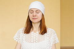 Portrait of red-haired woman in a hat for yoga with closed eyes i stock photography
