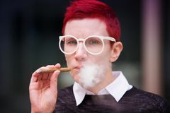 Portrait of red-haired woman smoking a cigar Royalty Free Stock Image