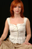 Portrait Of Red Head In White Blouse. Portrait of female sitting, wearing white cotton blouse and brown skirt Stock Images