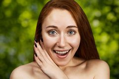 Portrait of a redhead young girl sharing a secret and gossip with her mouth open. Portrait of red head young girl sharing a secret and gossip with her mouth open stock image