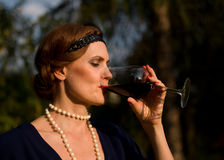 Portrait - The Red Wine Lady in the garden - 1930 Style. The Russian Lady - 1930 Style - is drinking the red wine in the garden stock image