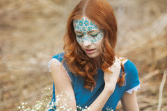 Portrait of redhair girl in blue dress in the spring forest. Portrait of girl in blue dress in the spring forest. Model have unusual makeup on face Stock Photography