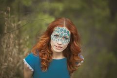 Portrait of redhair girl in blue dress in the spring forest. Portrait of girl in blue dress in the spring forest. Model have unusual makeup on face Stock Images