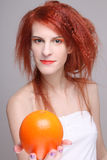 Portrait of redhaired girl with orange. Portrait of young curly redhaired woman with orange Stock Photo