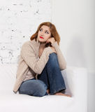 Portrait of the redhaired woman. On the sofa Stock Photos