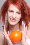 Portrait of redhaired woman with orange. Portrait of young redhaired woman with orange Royalty Free Stock Images