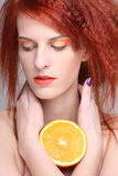 Portrait of redhaired woman with orange half. Portrait of young redhaired woman with orange half Stock Photos