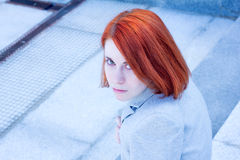 Portrait of redhead attractive woman sitting outside on the stairs Stock Images