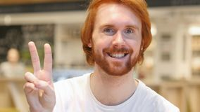 Portrait of Redhead Beard Man Gesturing Victory Sign in Cafe. 4k , high quality royalty free stock image