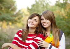 Portrait of redhead and brunette girls at outdoor. Stock Photos