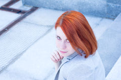 Portrait of redhead business attractive woman with smile sitting outside on the stairs Royalty Free Stock Image