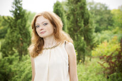 Portrait of redhead girl with blue eyes on nature Royalty Free Stock Photos