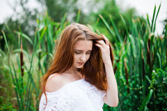 Portrait of redhead girl in countryside with bulrush background Stock Photography