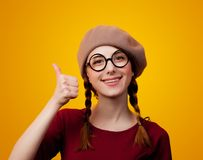 Portrait of redhead girl with eyeglasses and beret. On yellow background Royalty Free Stock Photography