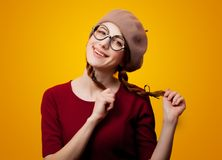 Portrait of redhead girl with eyeglasses and beret. On yellow background Stock Photography