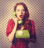 Portrait of a redhead girl with green dial phone Stock Image