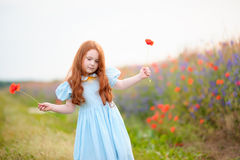 Portrait redhead little child with two wild flowers at hands sta Stock Image