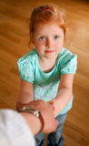 Portrait of redhead little girl. Rdehead little girl with blue eyes holding a hand of adult looking up Royalty Free Stock Image