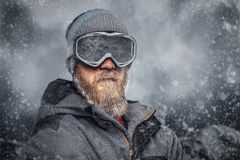 Portrait of a redhead snowboarder with a full beard in a winter hat and protective glasses dressed in a snowboarding. Coat posing against the background of royalty free stock photo