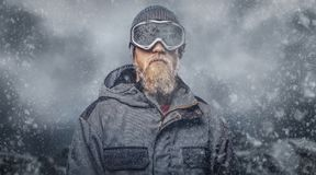 Portrait of a redhead snowboarder with a full beard in a winter hat and protective glasses dressed in a snowboarding. Coat posing against the background of stock image