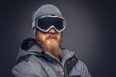 Portrait of a redhead snowboarder with a full beard in a winter hat and protective glasses dressed in a snowboarding. Coat posing at a studio, looking away stock image