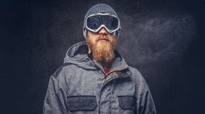 Portrait of a redhead snowboarder with a full beard in a winter hat and protective glasses dressed in a snowboarding. Coat posing at a studio, looking away stock photo