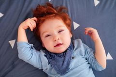 Portrait of redhead toddler baby boy laying on bed sheets Royalty Free Stock Photography