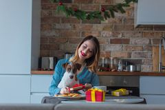 Portrait of redhead woman with dog at kitchen Royalty Free Stock Photography