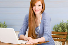 Portrait redhead woman with laptop on terrace Stock Image