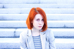 Portrait of redhead woman sitting outside on the stairs Stock Photography