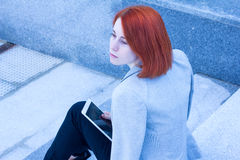 Portrait of redhead woman sitting on the street on the stairs with tablet Royalty Free Stock Photos