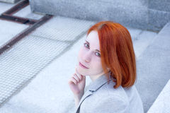 Portrait of redhead woman with smile sitting outside on the stairs Stock Photos