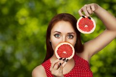 Portrait of a redhead young girl covering her mouth with half a red grapefruit royalty free stock photography