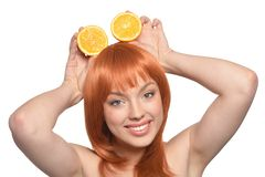 Portrait of a redhead young woman with orange halves. Isolated on white background royalty free stock photo