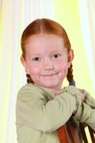 Portrait Redheaded Girl. Closeup portrait shot of a smiling redheaded girl with braids.  Sitting backwards on a chair, arms crossed at top of chair, in profile Royalty Free Stock Photo