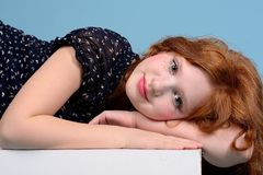 Portrait of a redheaded girl in black dress lies Royalty Free Stock Photography