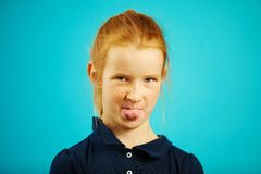 Portrait of redheaded girl showing tongue at the camera over blue background. royalty free stock photos