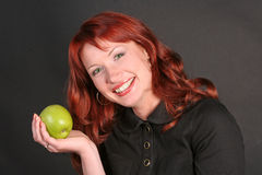 Portrait of redheaded woman with an apple Royalty Free Stock Photo