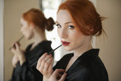 Portrait of a redheaded woman applying lip liner Stock Images