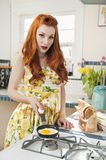 Portrait of a redheaded woman preparing omelet Royalty Free Stock Photos