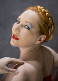 Portrait of a redheaded woman. Portrait in profile redheaded woman on a grey background Royalty Free Stock Photography