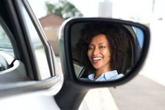 Reflection in side mirror of smiling african woman driving car. Portrait of reflection in side mirror of smiling african woman driving car Stock Images