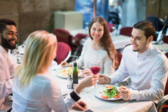 Portrait of relaxed adults having dinner outdoors. And laughing Royalty Free Stock Photo