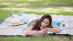 Brunette girl sleep or nap in park. Portrait of relaxed Asian beautiful girl sleep or nap on mat at grass field while hold smartphone with copy space for text royalty free stock photography