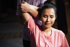 Thai massage to Beautiful tan woman. Portrait of relaxed Asian beautiful woman massaging elbow and arm by professional massager in spa salon. Body care treatment royalty free stock images